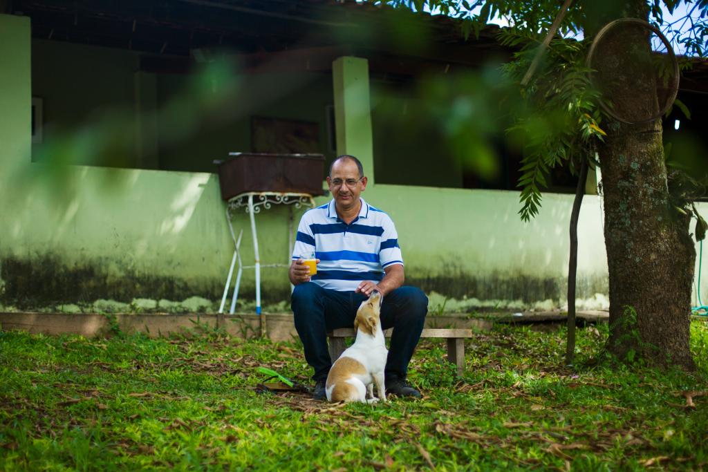 Ademir sentado com seu cachorro do lado de fora de casa.
