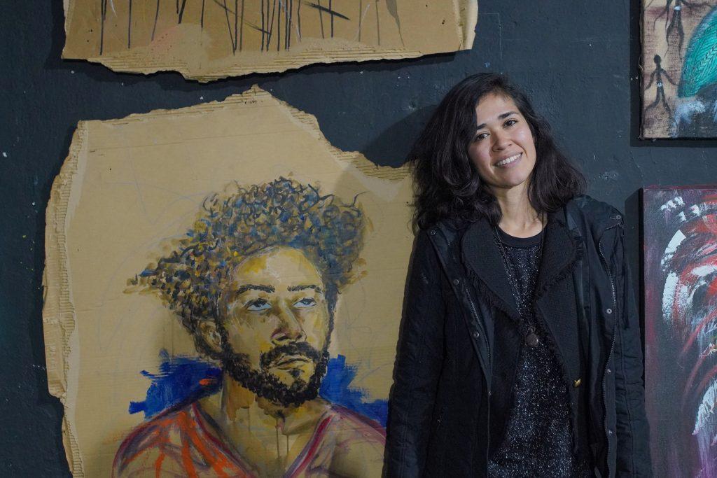 Moara Brasil ao lado de seu quadro em homenagem a Sirius Amen, residente do oitavo andar.